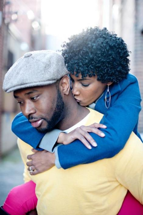 black woman kissing man on neck